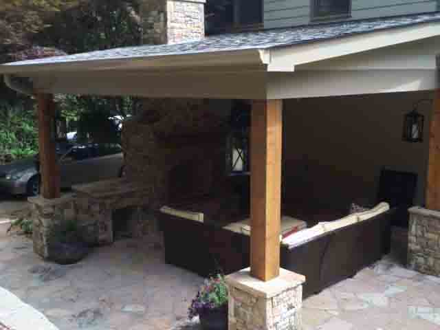 Stone patio extension with roof and outdoor fireplace